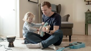 Man and daughter playing guitar