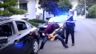 Rob Scallon playing guitar next to a police car