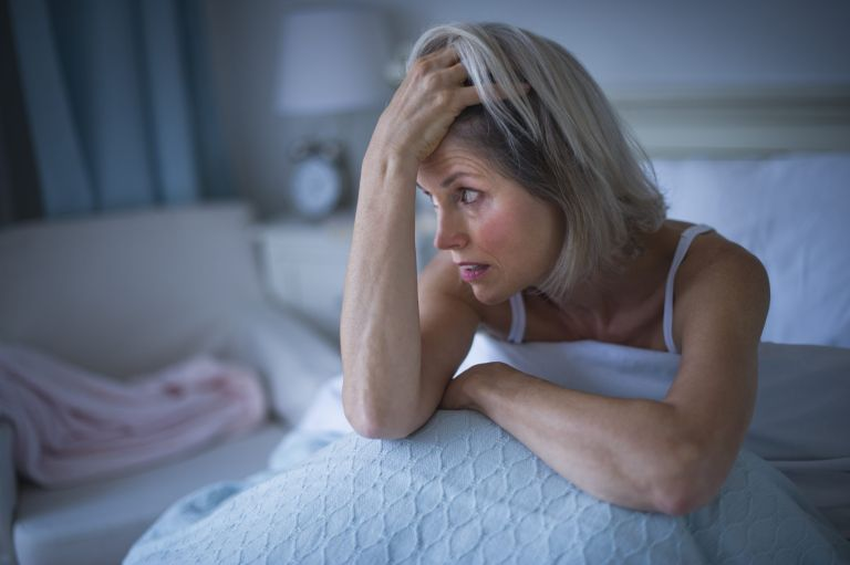woman sitting up in bed at at night