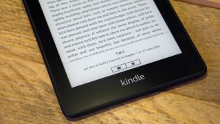 The bottom half of a Kindle Paperwhite on a wooden surface