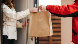 A deliveryman hands a bag to a woman waiting at her front door.