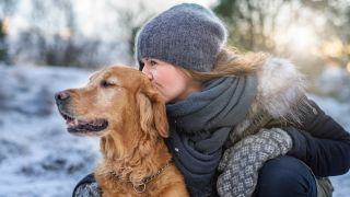 Woman all rugged up in winter clothing outside in the snow kissing the head of her Golden Retriever