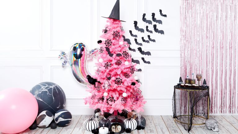 Pink Christmas tree decorated for Halloween using witches hat topper, adhesive bats on walls, silver foil ghost balloon, monochrome painted pumpkins
