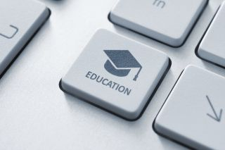 "Close of of computer key labeled ""education"" with graduation cap and mortarboard."