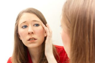 Young woman examining her face in the mirror