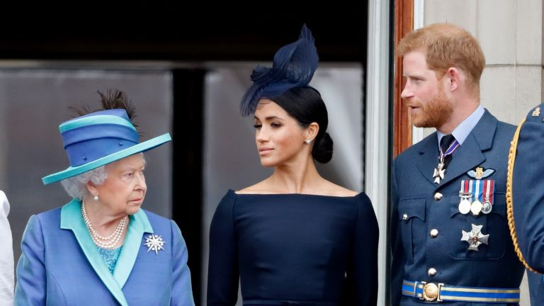 Queen Elizabeth II, Meghan, Duchess of Sussex and Prince Harry, Duke of Sussex watch a flypast to mark the centenary of the Royal Air Force from the balcony of Buckingham Palace on July 10, 2018 in London, England