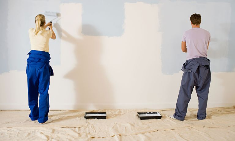 Couple painting a wall with blue