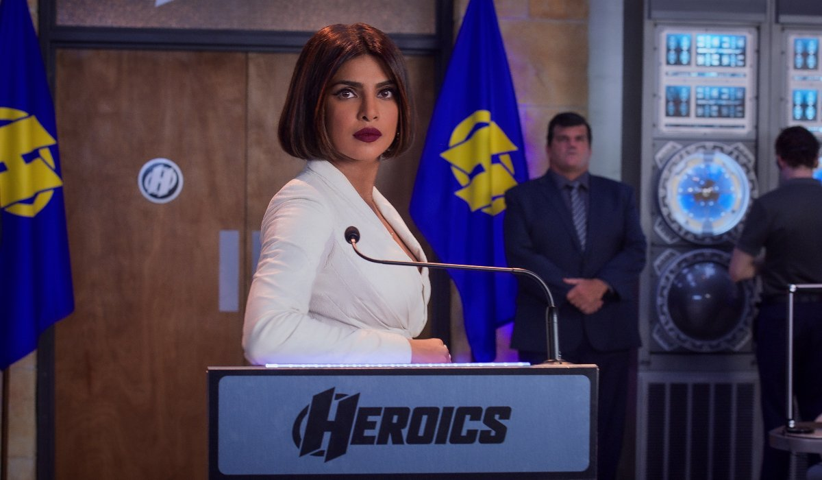Priyanka Chopra Jones stands well dressed at a podium in We Can Be Heroes.