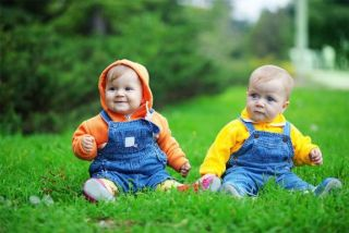 two babies sitting in grass
