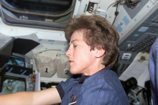 NASA astronaut Wendy Lawrence works at the space shuttle Discovery's aft flight deck during the STS-114 mission, on July 28, 2005.