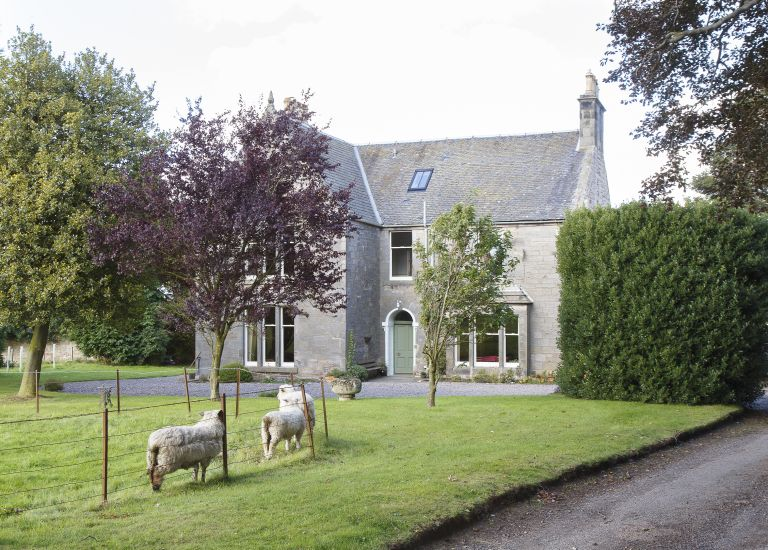 exterior of a georgian home with sheep in the foreground