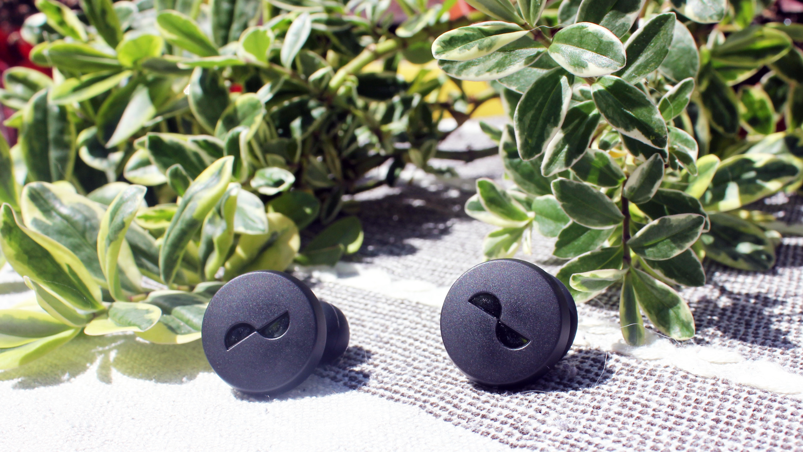 the nuratrue earbuds on an outdoor table with plants in the background