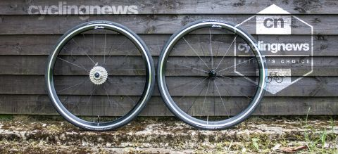 Scribe Pace rim brake wheels resting against a wooden backdrop