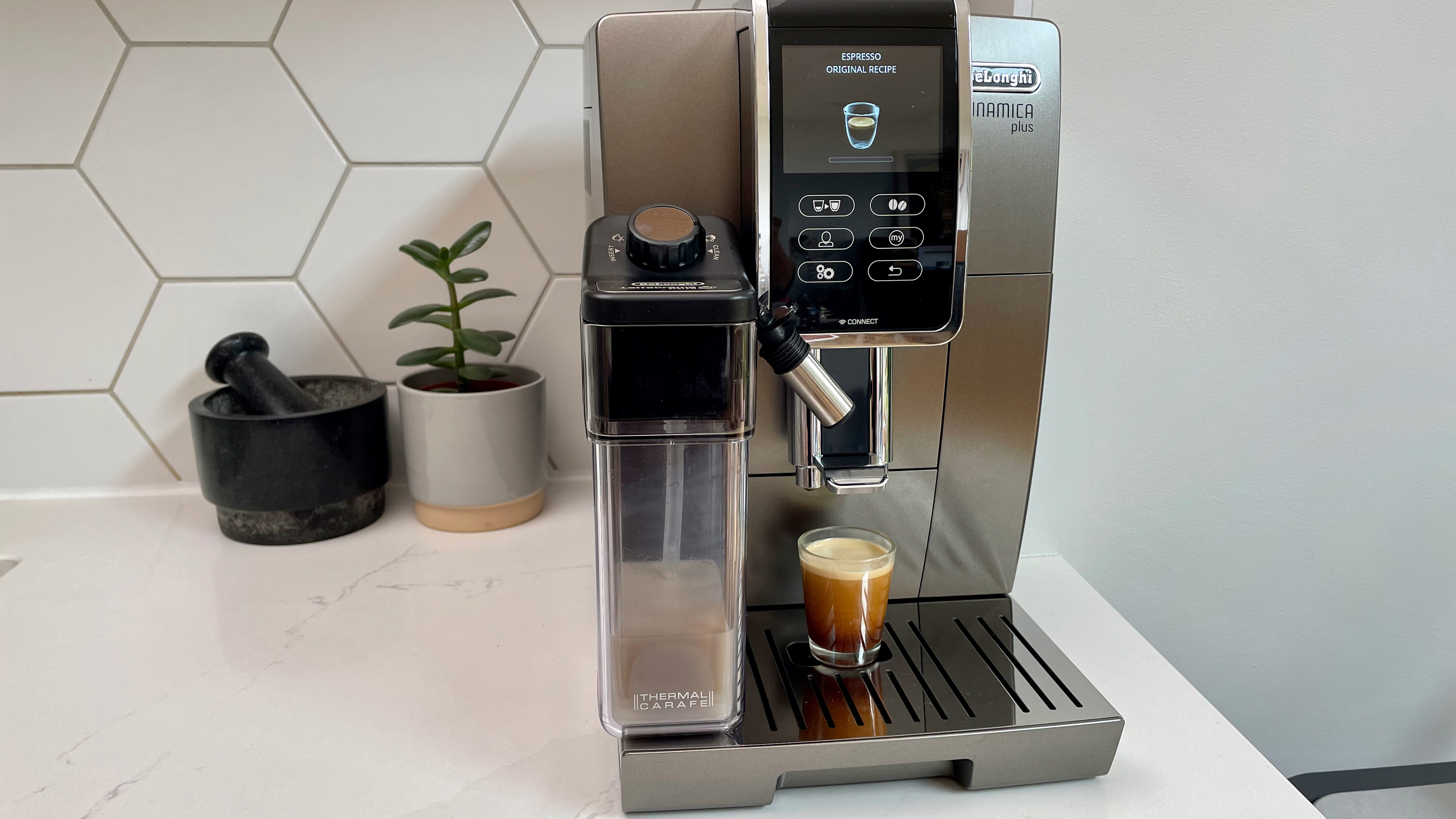 De'Longhi Dinamica Plus on a kitchen countertop being used to make an espresso
