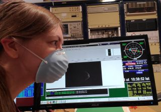 Anne Virkki, head of Planetary Radar at the Arecibo Observatory in Puerto Rico, wears her face mask with a doppler radar image of asteroid 1998 OR2.