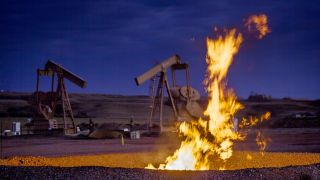 A fire burns in a pit near a natural gas well as methane (CH4) escapes into the atmosphere.