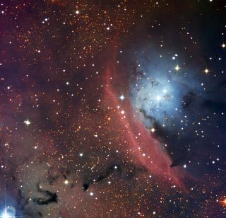 a red and blue interstellar cloud shines in Sagittarius