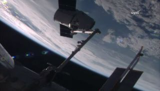 An unmanned Dragon space capsule is seen captured by a robotic arm at the International Space Station as it delivered fresh supplies to the outpost's crew on July 20, 2016.