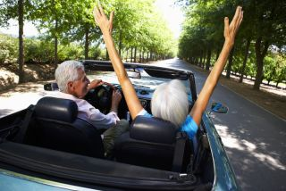 An older couple happily takes a spin in a convertible.