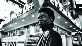 A black and white picture of Charles Bradley standing outside a New York Police Department building.