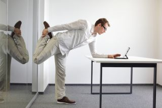 A man stands at his desk, and stretches out his quads as he works.