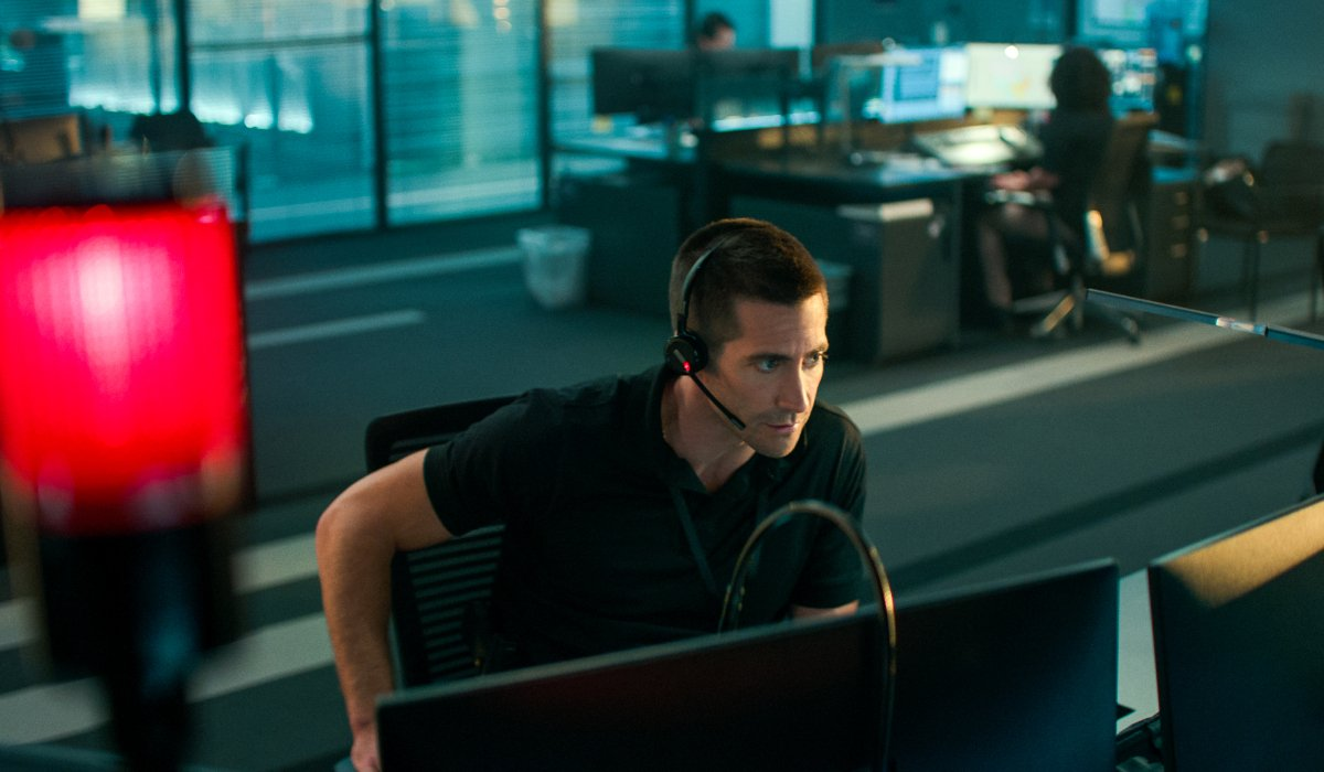 Jake Gyllenhaal sitting at his 911 station, taking a call in The Guilty.