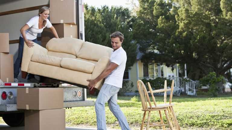 couple moving sofa from a moving van
