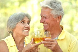 An older couple toasts with glasses of white wine