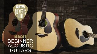 3 Yamaha acoustic guitars lined up with one on its side
