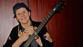 A photograph of Trevor Rabin holding a guitar and smiling