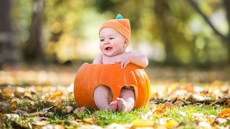Baby Halloween costume 2021—a baby sitting in a pumpkin
