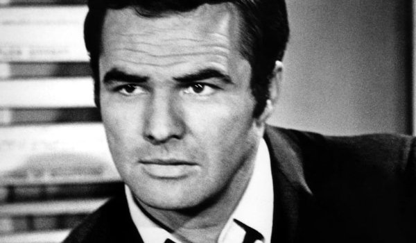 Dan August Burt Reynolds sitting in his office, with an open collar