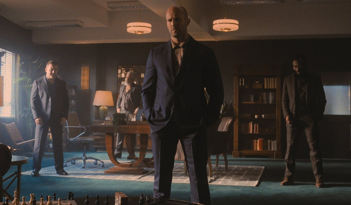 Jason Statham and his criminal associates stand in his office in Wrath of Man.