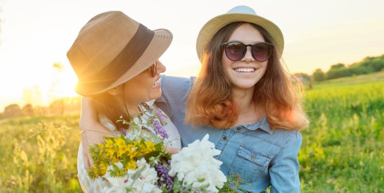 Mothers day, hugging happy smiling daughter with mother in meadow with bouquet of spring flowers