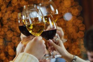 People raise wine glasses to toast