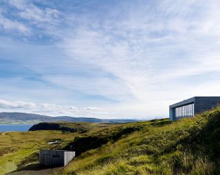 A self build in Skye with a low lying roof which blends into the landscape