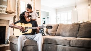 Father plays guitar to his daughter