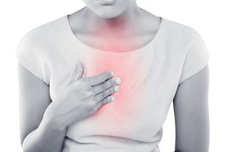 A woman's chest fills with the pain of heartburn