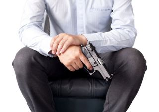 A man in a suit holding a gun.