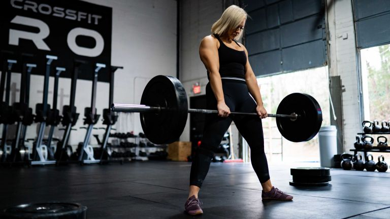 person using the best barbell to build strength in a gym by doing deadlifts