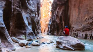 A hiker in a red shirt sits on a rock in the Narrows gorge Zion