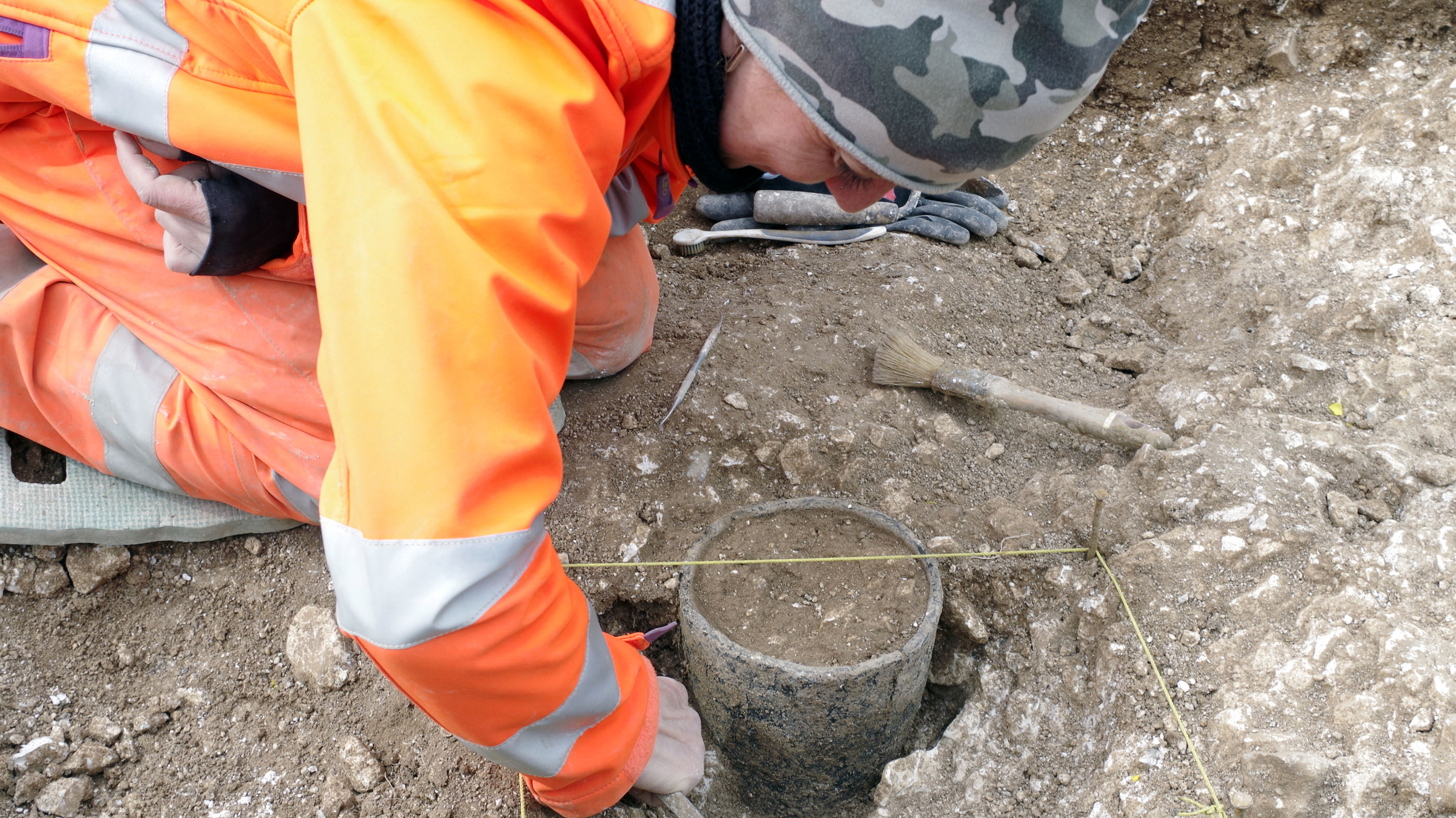 An archaeologist with Wessex Archaeology excavates a Bronze Age pot discovered during preliminary work on the site of the proposed tunnel near Stonehenge.