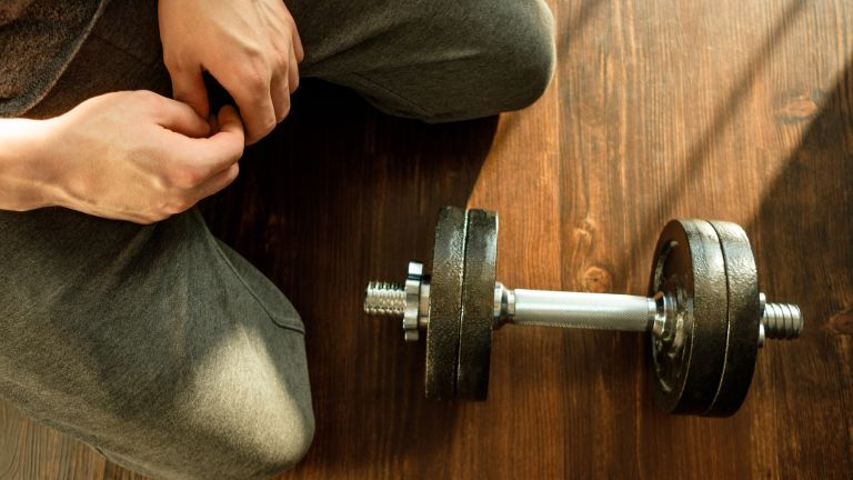 Person kneeling down by best adjustable dumbbell