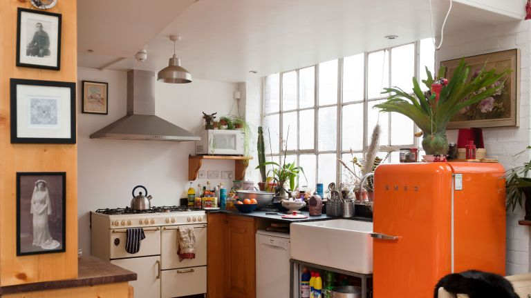 kitchen with orange fridge and a microwave