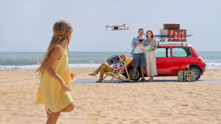 best beginner drone: family flying a DJI mini 2 drone on a beach