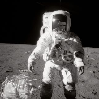 Astronaut Alan L. Bean, Apollo 12, walks on the Moon's surface. Commander Charles Conrad Jr. is reflected in Bean's helmet visor.