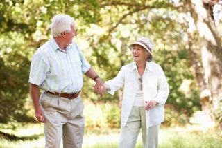 An older couple walks together, holding hands.