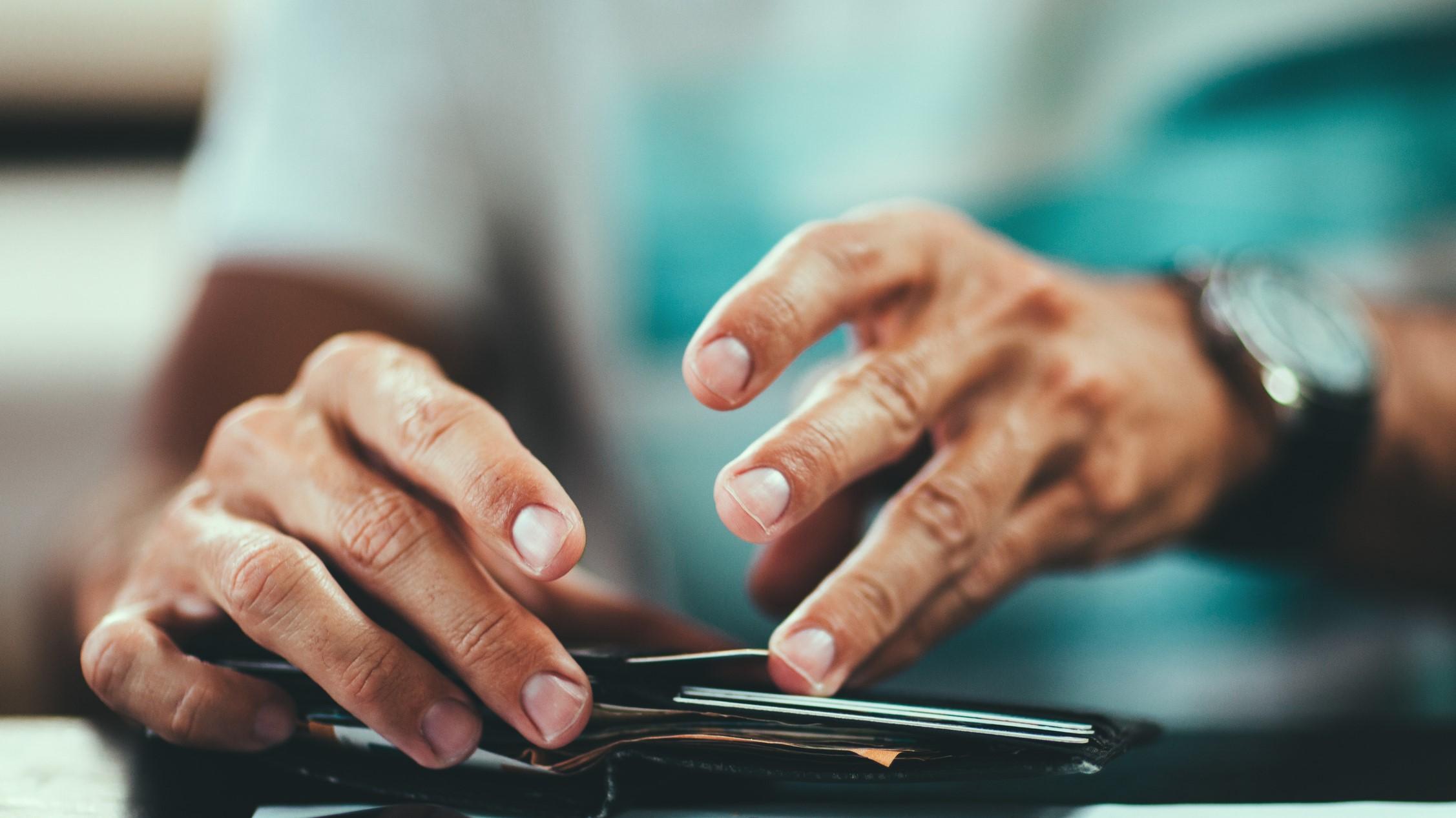 Man looks through wallet