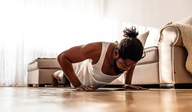 Man doing a HIIT workout in his front room