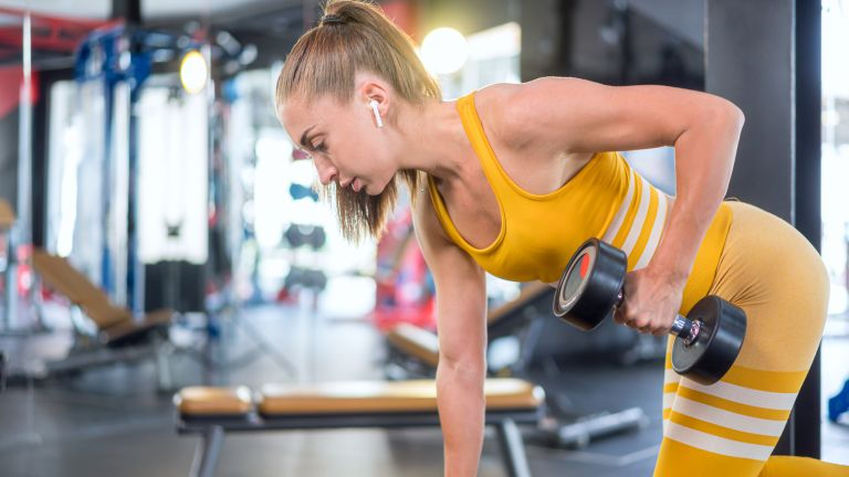 woman exercising with the best workout earbuds